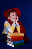 Little boy in colorful clothes dreaming. Blond little boy in read beret and scarf sitting with a pile of colorful books on blue background Royalty Free Stock Images