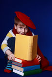Little boy in colorful clothes reading a book. Blond little boy in red beret and scarf sitting with a pile of colorful books on blue background Royalty Free Stock Image