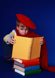 Little boy in colorful clothes reading a book. Blond little boy in read beret and scarf sitting with a pile of colorful books on blue background Stock Images