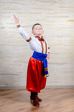Little boy in colorful costume doing folk dancing Stock Photos