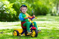 Little boy on colorful tricycle Stock Image