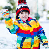 Little  boy in colorful winter clothes playing with snowman, out. Little funny kid boy in colorful winter clothes having fun with playing with snow ball fighting Royalty Free Stock Image