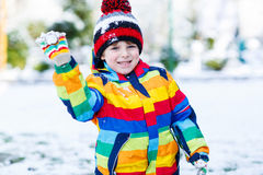 Little  boy in colorful winter clothes playing with snowman, out. Little funny kid boy in colorful winter clothes having fun with playing with snow ball fighting Royalty Free Stock Photos