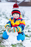 Little  boy in colorful winter clothes playing with snowman, out. Little funny kid boy in colorful winter clothes having fun with snow and snowman, outdoors Stock Photography