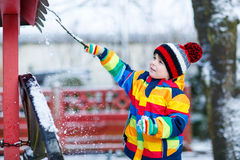 Little  boy in colorful winter clothes playing with snowman, out. Little funny kid boy in colorful winter clothes having fun with playing with snow, outdoors Royalty Free Stock Images
