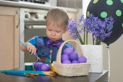 Little boy coloring easter eggs stock photography