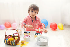 Little boy, coloring eggs for Easter at home Royalty Free Stock Photography