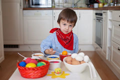 Little boy, coloring eggs for Easter at home Royalty Free Stock Photos