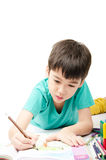Little boy coloring image lay on the floor in concentrate Royalty Free Stock Images