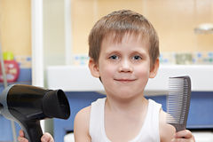 Little boy with a comb and hair dryer Stock Image