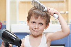 Little boy with a comb and hair dryer Royalty Free Stock Images
