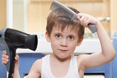 Little boy with a comb and hair dryer Stock Photography