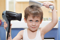 Little boy with comb and hair dryer Royalty Free Stock Photography