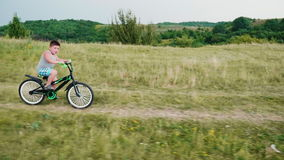 A little boy comes down from a hill on a bicycle, smiling. Carefree childhood in rural areas stock footage