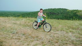A little boy comes down from a hill on a bicycle, smiling. Carefree childhood in rural areas stock video footage