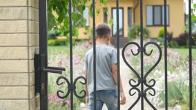 Little boy coming home, opening, closing gate, yard, summer