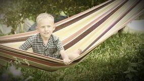 Little Boy con sonrisa encantadora en cantidad de la hamaca almacen de metraje de vídeo