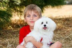 Little Boy con un cane di bianco dell'animale domestico Fotografia Stock