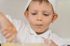 Little boy concentrating as he bakes a cake Stock Photography