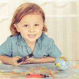 Little boy considering a world map with a magnifying glass Stock Images