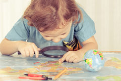 Little boy considering a world map with a magnifying glass Royalty Free Stock Images