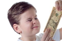The Little boy considers a denomination. The little boy holds money in hands and attentively them considers Royalty Free Stock Photos