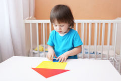 Little boy constructing house of paper details Royalty Free Stock Image