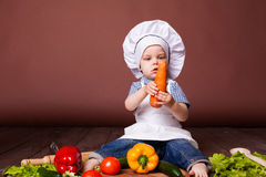 Little boy Cook carrots, peppers, tomatoes, lettuce, Royalty Free Stock Image