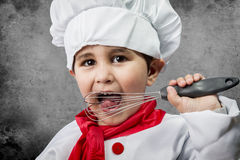 A little boy cook in uniform over vintage  background Royalty Free Stock Photography
