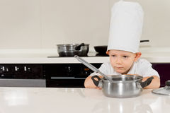 Little boy cooking bending down to smell the food Royalty Free Stock Image