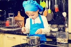Little boy cooking in kitchen interior Royalty Free Stock Images
