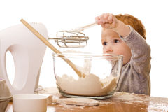 Little boy cooking and making mess in kitchen. Little boy loose in kitchen playing with beater and mixing bowl royalty free stock images