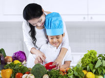 Little boy cooking with mother Stock Photos