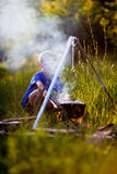 Little boy cooks on a fire in wood Royalty Free Stock Photography