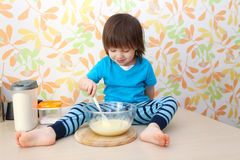Little boy cooks sitting on a table Royalty Free Stock Photography