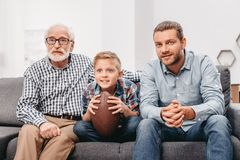 Little boy on couch with grandfather and father, cheering for a football game and holding a. Football ball stock photography
