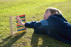 Little boy counting on an abacus. Little boy lying and counting on the colorful abacus stock photos