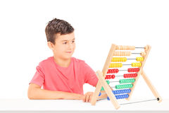 Little boy counting on abacus seated at a table Stock Photo