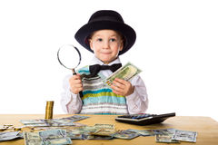 Little boy counting money on the table. Little boy in black hat counting money on the table, isolated on white Royalty Free Stock Photos