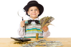 Little boy counting money on the table. Smiling little boy in black hat counting money on the table, isolated on white Royalty Free Stock Photo