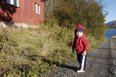 Little boy on country road. A little boy on a country dirt road near a red barn stock photography