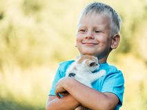 Little boy at countryside holding his lovely fluffy kitty cat. Pets and lifestyle concept stock images