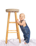 Little Boy in Coveralls Standing by Stool Royalty Free Stock Photos