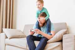 Little boy covering father eyes while he playing computer games. Smiling little boy covering eyes of his father while he playing computer games on sofa at home stock photo