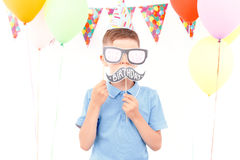 Little boy covering his face with birthday tags Royalty Free Stock Image
