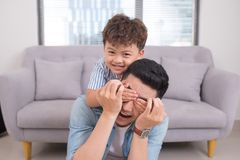 Little boy covers his dad eyes while playing at home Royalty Free Stock Image