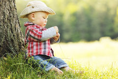 Little boy in a cowboy hat playing on nature Stock Photo