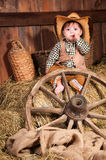 Little boy in cowboy hat, a waistcoat and a plaid shirt sitting in the hay Stock Photo