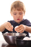 Little boy cracking an egg. Isolated on white Stock Photo