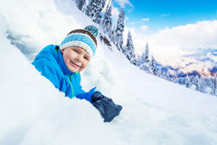 Little boy crawl out of snow cave in park Royalty Free Stock Image